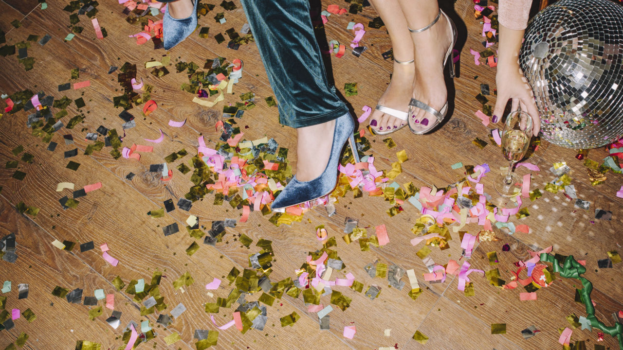 Party with confetti on the dancefloor, a disco ball and two people wearing heels.