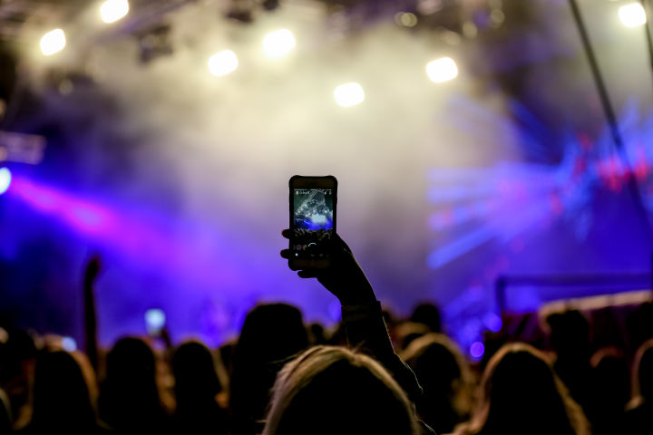 A person taking a photo on their photo at a live music event.