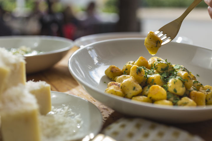 Gnocchi served next to a platter of cheeses.